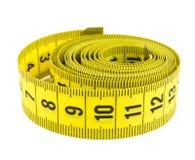 Nastro di misurazione arricciato di colore giallo Fotografia Stock
