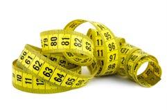 Nastro di misurazione arricciato di colore giallo su priorità bassa bianca Immagine Stock