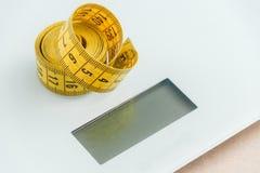 Nastro di misurazione curvo Vista del primo piano del nastro di misurazione giallo sul pesatore Fotografia Stock