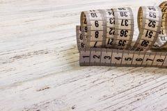 Nastro di misurazione del sarto alto di fine sul fondo di legno della tavola Reparto basso di misurazione bianco del nastro del c Fotografia Stock