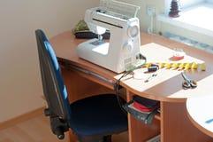 Nastro di misurazione, della macchina per cucire, bobine del filo e forbici sulla tavola di legno con luce solare immagini stock libere da diritti