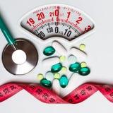 Nastro di misurazione dello stetoscopio delle pillole sulle scale Ritardi e braccia Immagine Stock Libera da Diritti