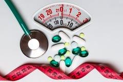 Nastro di misurazione dello stetoscopio delle pillole sulle scale Ritardi e braccia Fotografia Stock Libera da Diritti