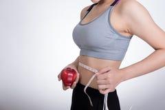 nastro di misurazione di forma fisica di uso sportivo della donna per misurare il yo della vita fotografie stock