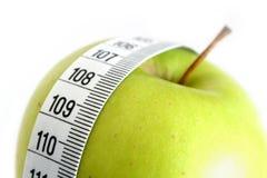 Nastro di misurazione e mela verde Fotografie Stock