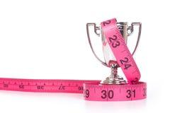Nastro di misurazione e piccola tazza di sport Fotografia Stock