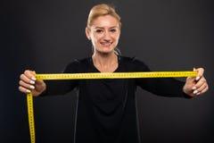 Nastro di misurazione e sorridere della palestra della tenuta femminile graziosa dell'istruttore Fotografia Stock