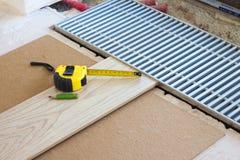Nastro di misurazione e una matita sulla plancia laminata del pavimento fotografia stock