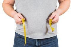 Nastro di misurazione giallo di misurazione della pancia dell'uomo maturo spesso isolato Fotografia Stock Libera da Diritti