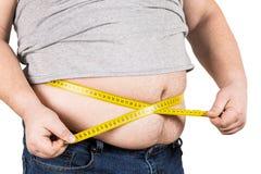 Nastro di misurazione giallo di misurazione della pancia dell'uomo maturo spesso isolato Immagini Stock