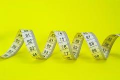 Nastro di misurazione su colore giallo Immagine Stock
