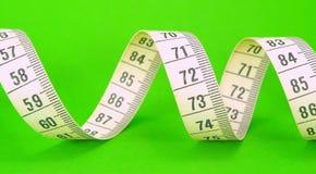Nastro di misurazione su verde Fotografia Stock