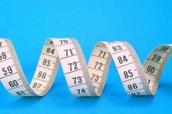 Nastro di misurazione sull'azzurro Immagine Stock