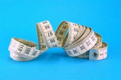 Nastro di misurazione sull'azzurro Immagini Stock Libere da Diritti