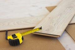 Nastro di misurazione sulla plancia laminata del pavimento fotografia stock libera da diritti