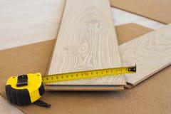 Nastro di misurazione sulla plancia laminata del pavimento immagini stock