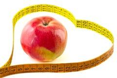 Nastro di misurazione un in forma di cuore con una mela rossa fotografie stock libere da diritti