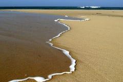 Nastro di schiuma sulla sabbia fotografie stock