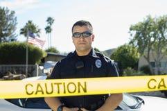 Nastro di Standing Behind Caution dell'ufficiale di polizia Immagine Stock