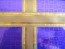 Nastro dorato in un arco viola sopra una priorità bassa bianca Fotografia Stock