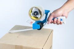 Nastro e contenitore d'imballaggio di mano Fotografie Stock