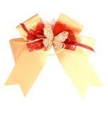 Nastro ed arco del regalo dell'oro su bianco Fotografia Stock