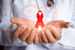 Nastro per la lotta contro l'AIDS nelle mani Fotografie Stock
