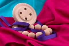 Nastro, perle e bottoni di legno sul tessuto Immagini Stock
