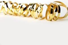 Nastro riccio metallico dell'oro su un fondo bianco Fotografia Stock Libera da Diritti