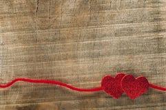 Nastro rosso del nastro e due cuori Immagini Stock