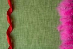 Nastro rosso e piume di uccello tinte sul fondo del tessuto Fotografie Stock Libere da Diritti