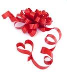 Nastro rosso ed arco del regalo isolati su bianco. Immagine Stock
