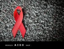 Nastro rosso su una pietra, concetto del nastro rosso di Giornata mondiale contro l'AIDS Fotografie Stock