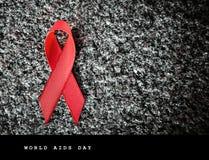Nastro rosso su una pietra, concetto del nastro rosso di Giornata mondiale contro l'AIDS Fotografia Stock Libera da Diritti