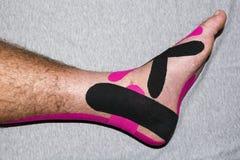 Nastro terapeutico elastico ed il professionista di cura dei piedi Fotografie Stock