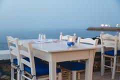Nastrojowy atmosferyczny wieczór na grka wybrzeżu, biel stoły w odpoczynku zdjęcia stock