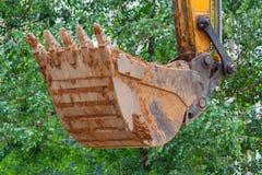 Nastroszony ekskawatoru wiadro na tle zielony drzewa zbliżenie zdjęcia royalty free