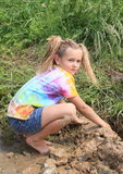 Nasty girl playing in mud. Happy little barefoot girl with ponytails playing in mud Royalty Free Stock Photography