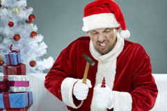 Nasty Santa. Wicked Santa breaking Christmas decorations with a hammer Stock Image