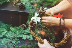 Naszywany widok decorator, tworzy Bożenarodzeniowego wianek jedlinowe gałąź, dekoracyjne jagody, sosna rożki i dekoracyjne zabawk Zdjęcia Royalty Free