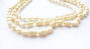 Natürliche Flussperlenperlen auf einer leichten Perlenhalskette auf einem weißen Hintergrund stockfoto