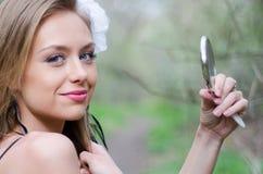 Natürlich schöne junge blonde Frau in der Natur, die einen Spiegel hält Stockfotografie