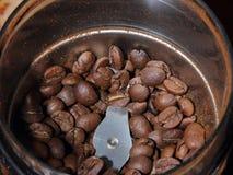 Natürliche aromatische Kaffeebohnen werden in eine Kaffeemühle für das Reiben gegossen, bevor man braut Stockbilder