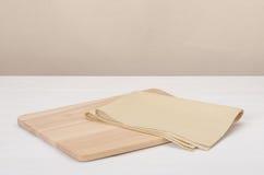Natürliche Baumwollserviette und hölzernes Brett auf Weiß Stockfotografie