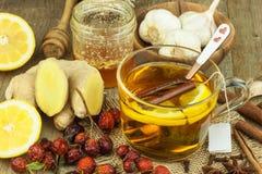 Natürliche Behandlung für Kälten und Grippe Ingwerzitronen-Honigknoblauch und Hagebuttentee gegen Grippe Heißer Tee für Kälten Ha Lizenzfreies Stockbild