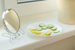 Natürliche Bestandteile für selbst gemachte Masken Gurke und Zitronenscheiben auf dem Fensterbrett zu Hause, mit Spiegel Hautpfle stockfotos