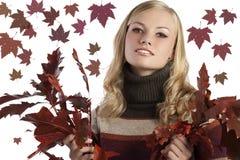 Natürliche blonde Schönheit, die einige Herbstblätter anhält Lizenzfreies Stockfoto