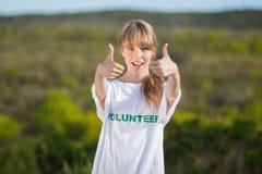 Natürliche Blondine, die ein freiwillig erbietendes T-Shirt aufgibt Daumen trägt Stockbild