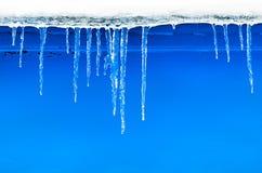 Natürliche Eiszapfen, die an einem blauen Hintergrund hängen Lizenzfreies Stockbild