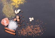 Natürliche Gewürze und Kräuter zerstreuten auf dunklen Hintergrund Natürliche und Biobestandteile für das Kochen lizenzfreies stockbild